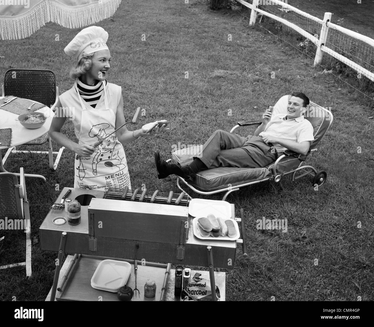 1950s 1960s WOMAN IN CHEF'S HAT AND APRON GRILLING HOT DOGS ON GRILL MAN IN CHAISE LONGUE LAUGHING EATING A FRANKFURTER Stock Photo