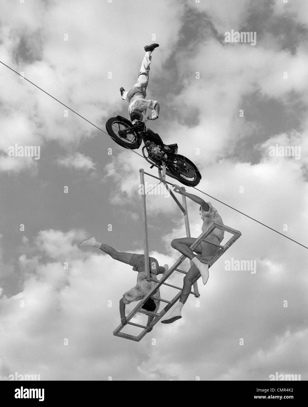 1950s 1960s HIGH-WIRE ACT WITH MAN STANDING ON HIS HEAD ON MOTORCYCLE WITH MAN AND WOMAN ON BALANCED LADDER SUSPENDED - Stock Image