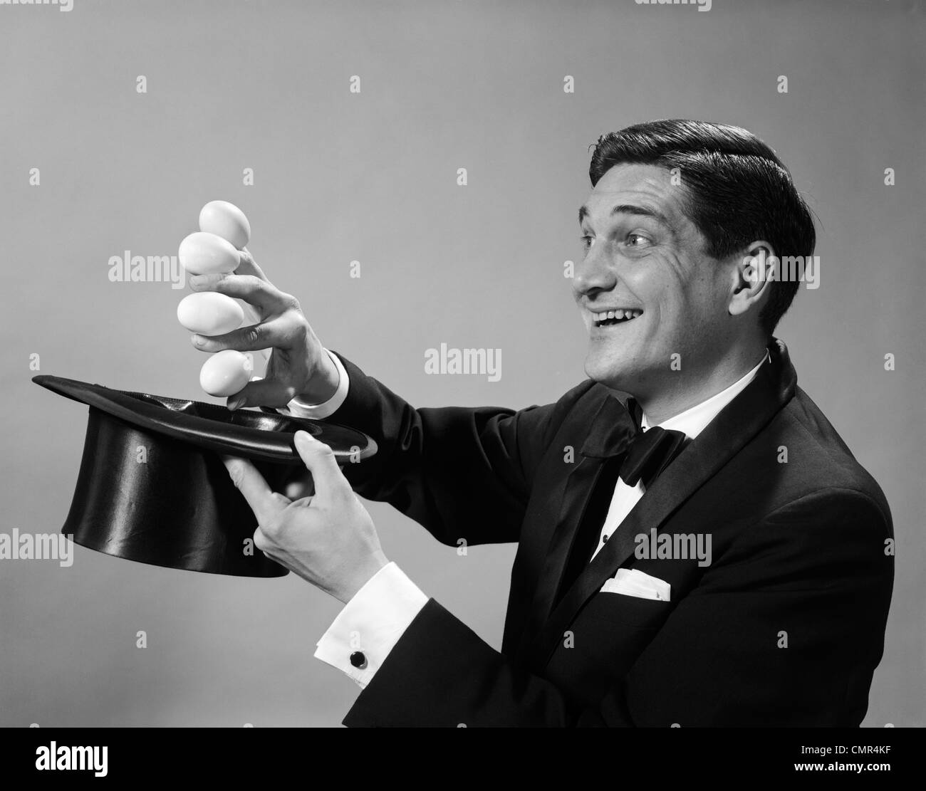 1960s PROFILE MAGICIAN MAN PULLING 4 EGGS OUT OF HAT HOLDING THEM BETWEEN FINGERS - Stock Image