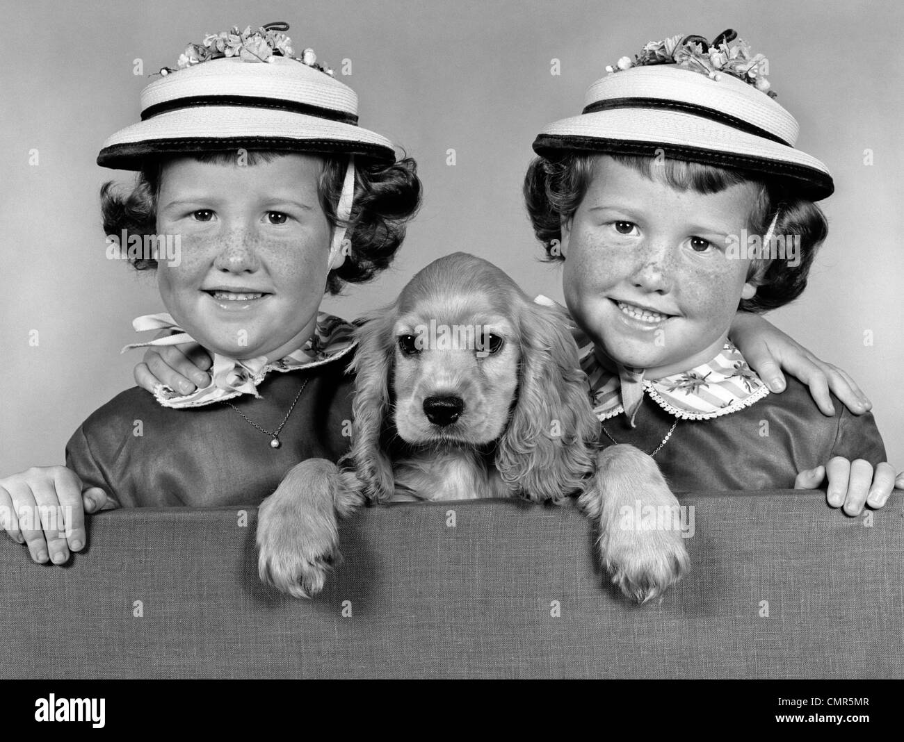 1950s 1960s TWIN GIRLS WEARING WHITE STRAW HATS SEPARATED BY A COCKER SPANIEL PUPPY LOOKING OVER A STUDIO FENCE - Stock Image