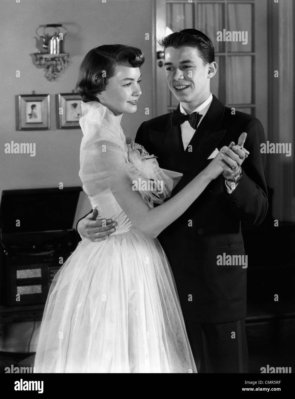 1950s SMILING TEENAGE COUPLE IN FORMAL EVENING WEAR DANCING INDOORS - Stock Image