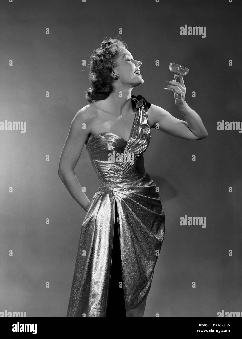 1950s WOMAN WEARING METALLIC EVENING GOWN HOLDING UP WINE GLASS PROFILE INDOOR - Stock Image