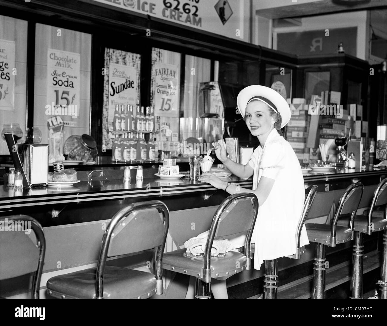 1930s WOMAN IN WHITE DRESS & HAT SITTING AT SODA FOUNTAIN COUNTER EATING ICE CREAM SUNDAE - Stock Image