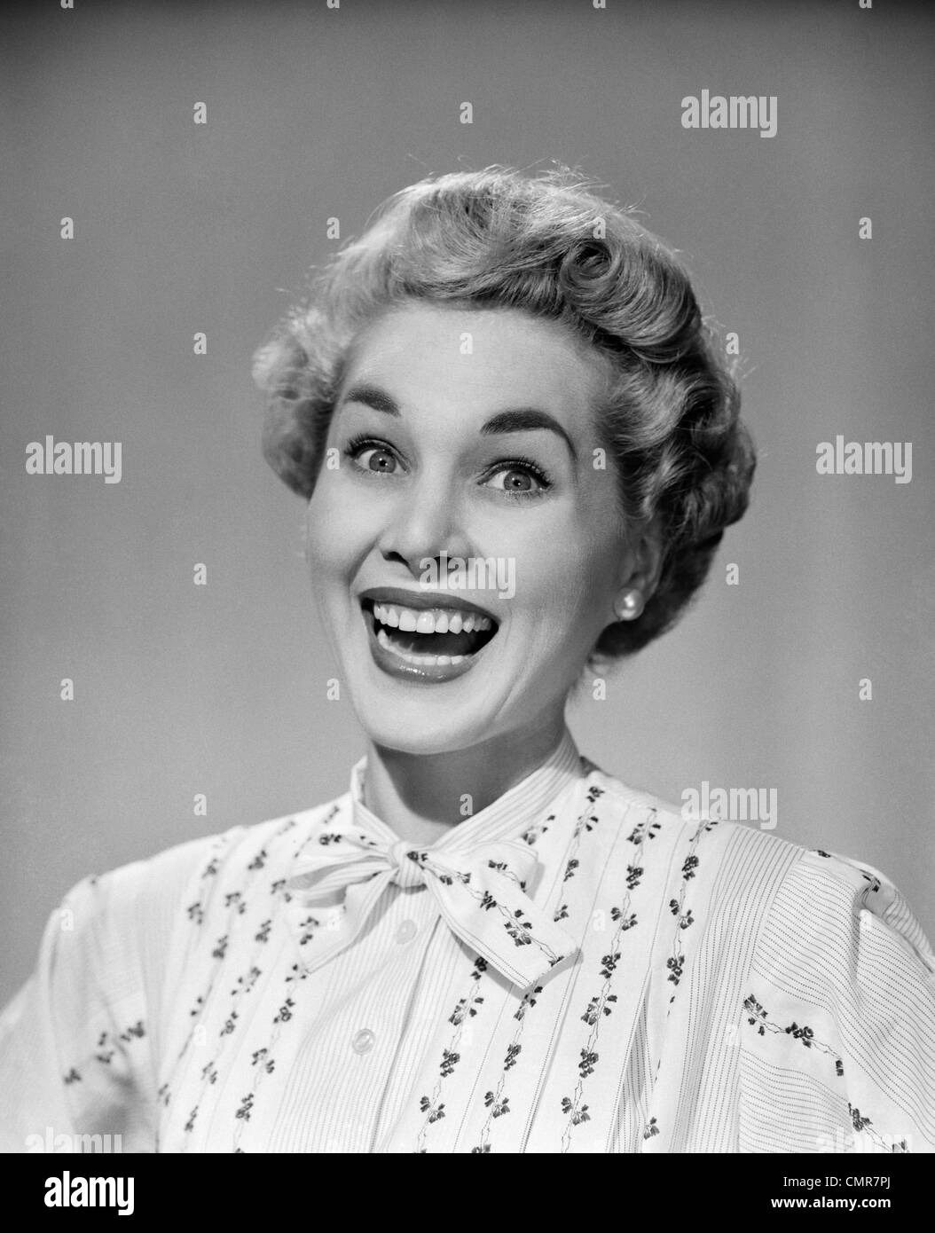 1950s PORTRAIT OF BLOND WOMAN EYES WIDE OPEN BIG SMILE HAPPY INDOOR LOOKING AT CAMERA - Stock Image