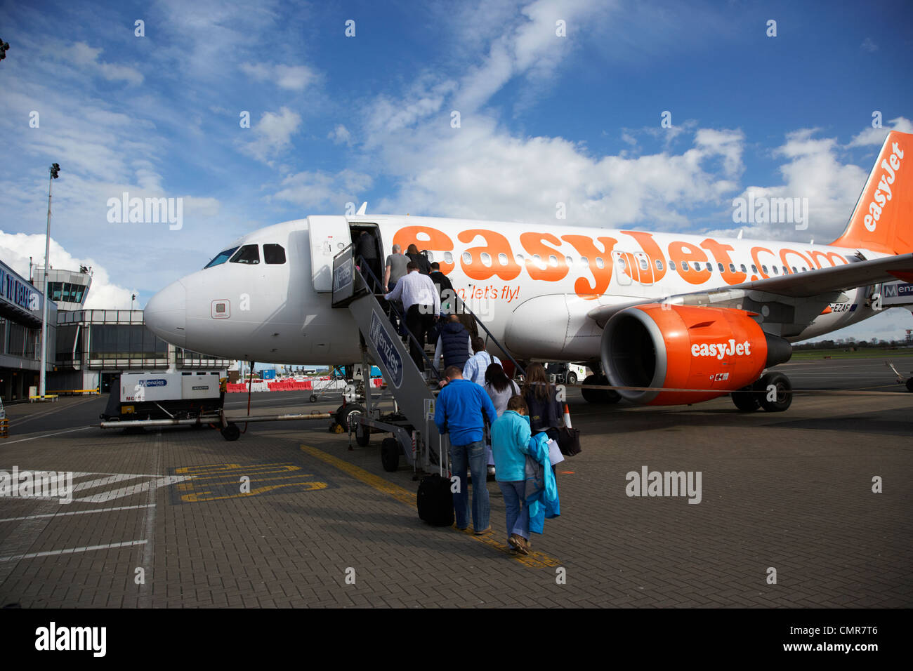 passengers boarding easyjet aircraft at belfast international airport northern ireland uk. - Stock Image