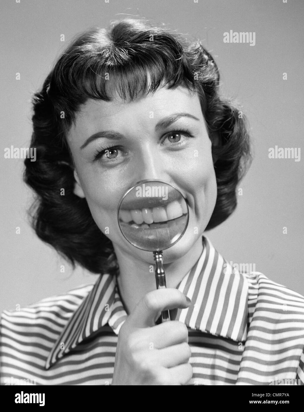 1950s SMILING PORTRAIT BRUNETTE WOMAN LOOKING AT CAMERA HOLDING MAGNIFYING GLASS TO MOUTH - Stock Image