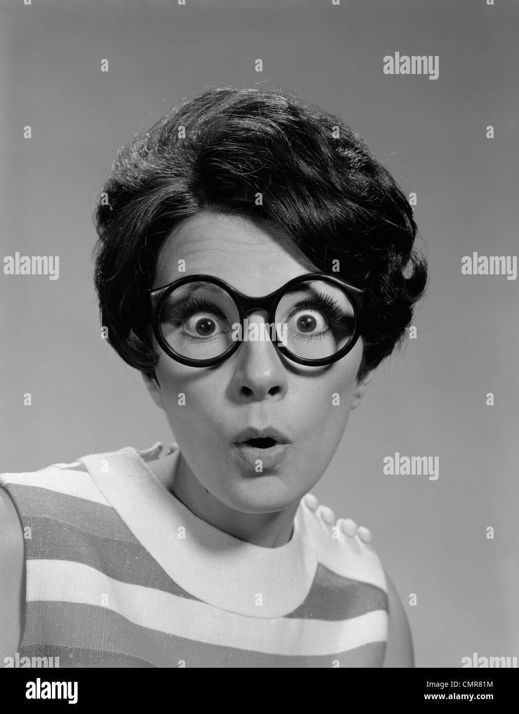 1960s PORTRAIT BRUNETTE WEARING DARK THICK ROUND EYEGLASSES WITH EYES WIDE OPEN - Stock Image