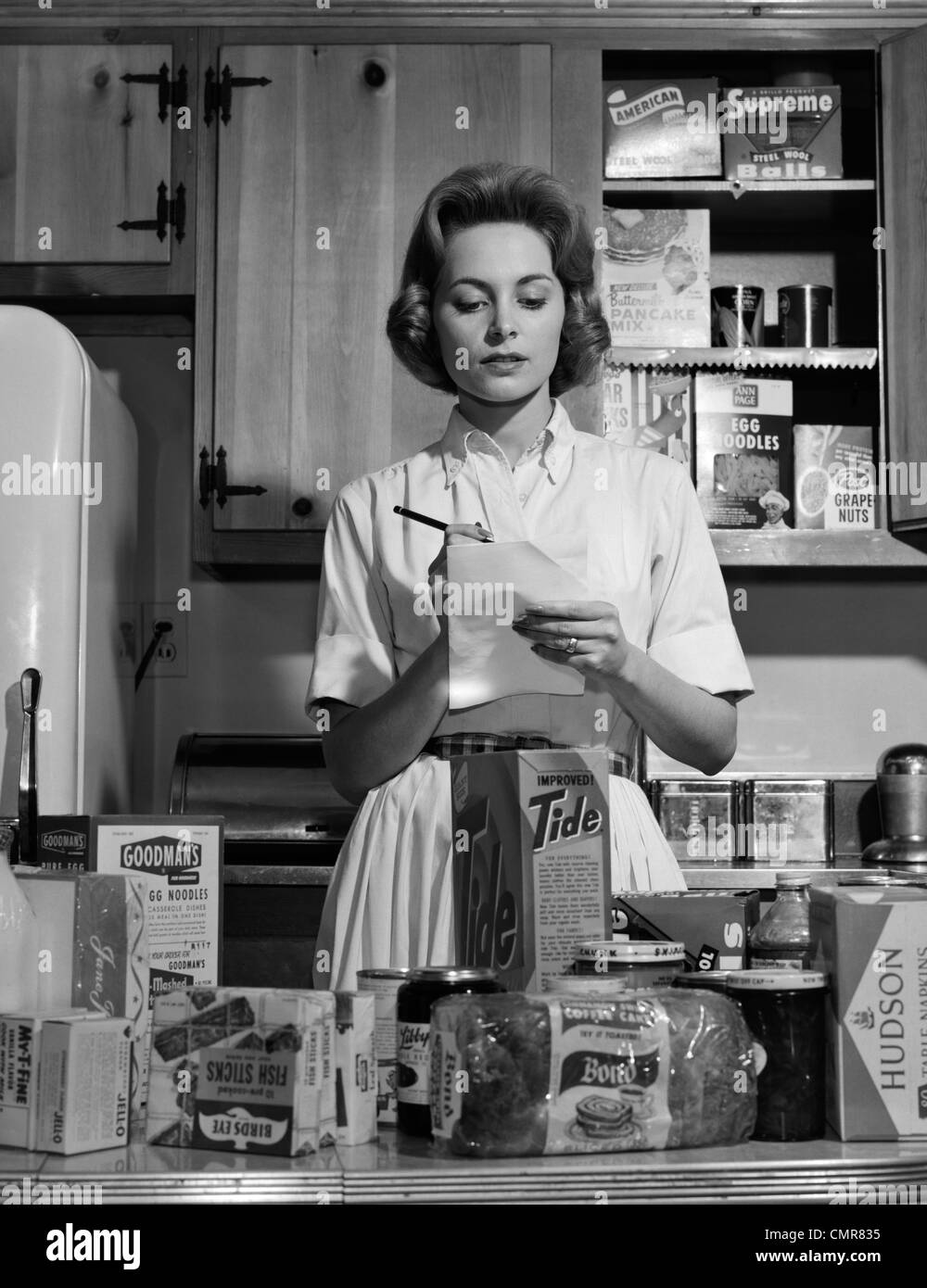 1960s Woman Housewife In Kitchen Checking Grocery Food