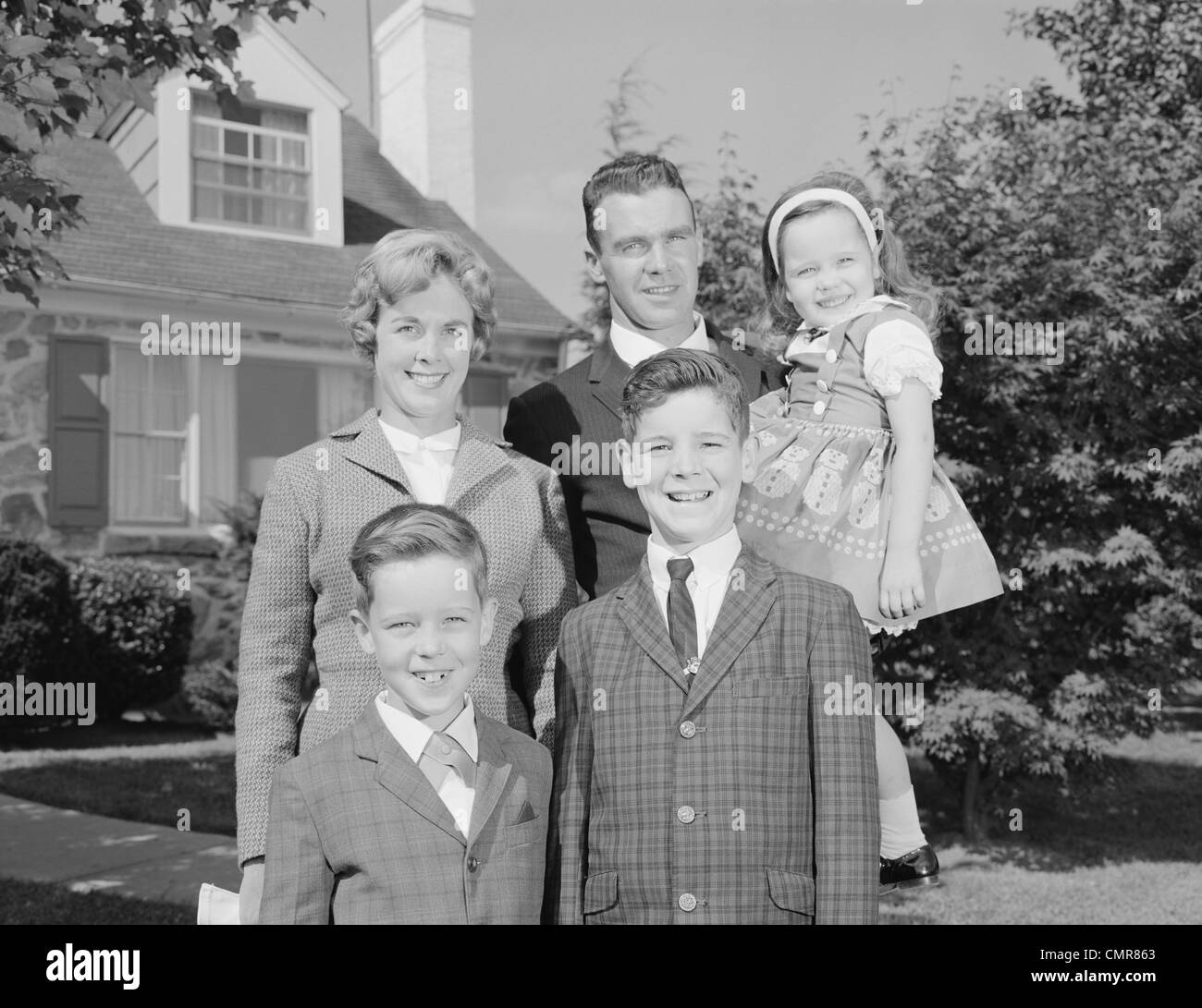 1960s FAMILY PORTRAIT FATHER MOTHER TWO SONS AND DAUGHTER IN FRONT OF SUBURBAN HOUSE LOOKING AT CAMERA - Stock Image