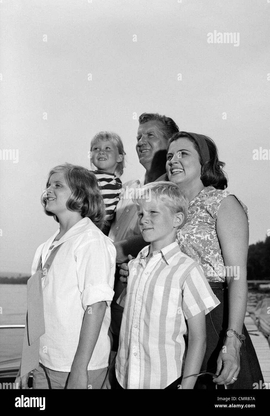 1960s SMILING FAMILY PORTRAIT FATHER MOTHER TWO DAUGHTERS SON STANDING TOGETHER OUTDOORS - Stock Image