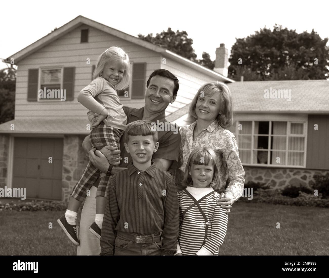 1960s FAMILY PORTRAIT OUTSIDE SUBURBAN HOUSE PARENTS 3 THREE KIDS - Stock Image