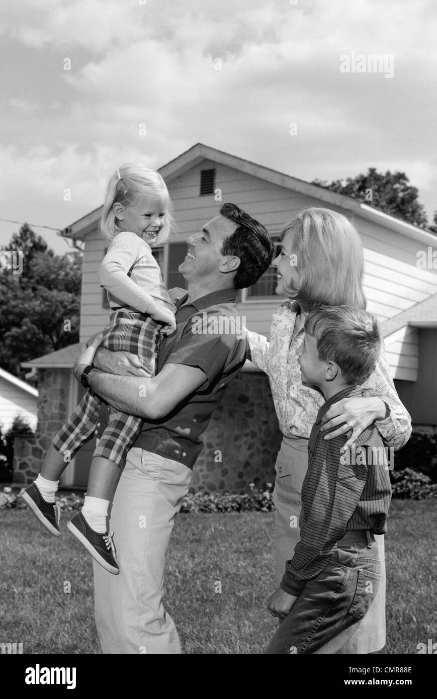 1960s FAMILY PORTRAIT FATHER DAUGHTER MOTHER SON IN YARD OF SUBURBAN HOUSE - Stock Image