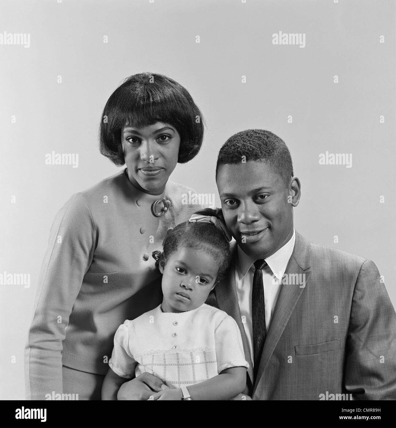 1960s AFRICAN AMERICAN FAMILY PORTRAIT FATHER MOTHER DAUGHTER LOOKING AT CAMERA - Stock Image