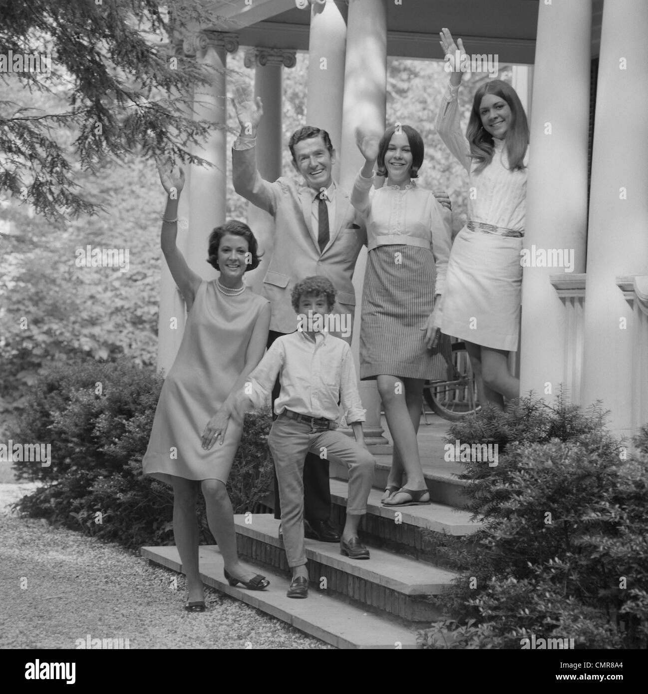 1960s FAMILY GROUP OF PEOPLE STANDING ON STEPS OF HOUSE WAVING - Stock Image