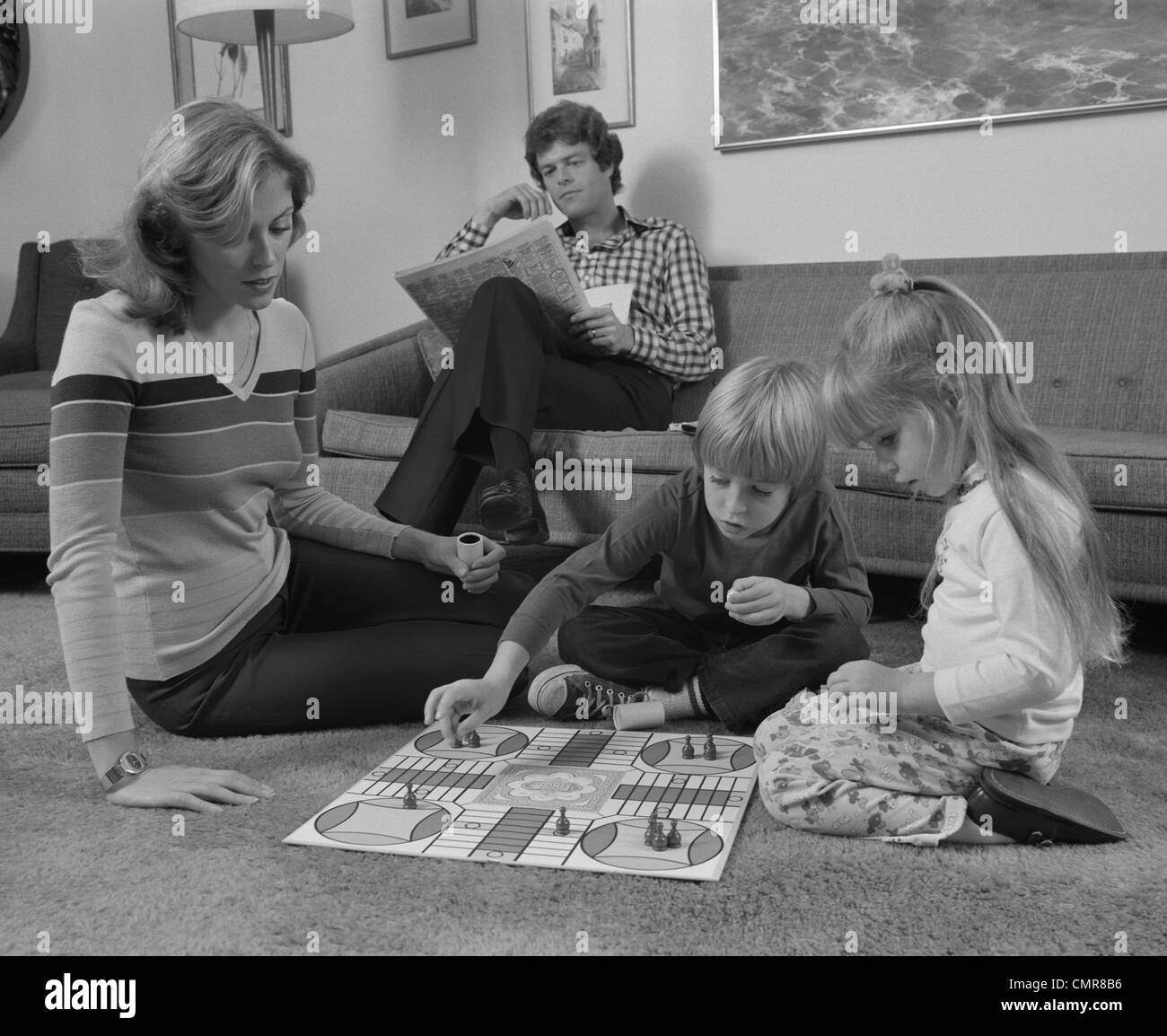 1970s FAMILY MOTHER KIDS PLAYING BOARD GAME LIVING ROOM FLOOR FATHER READING NEWSPAPER - Stock Image