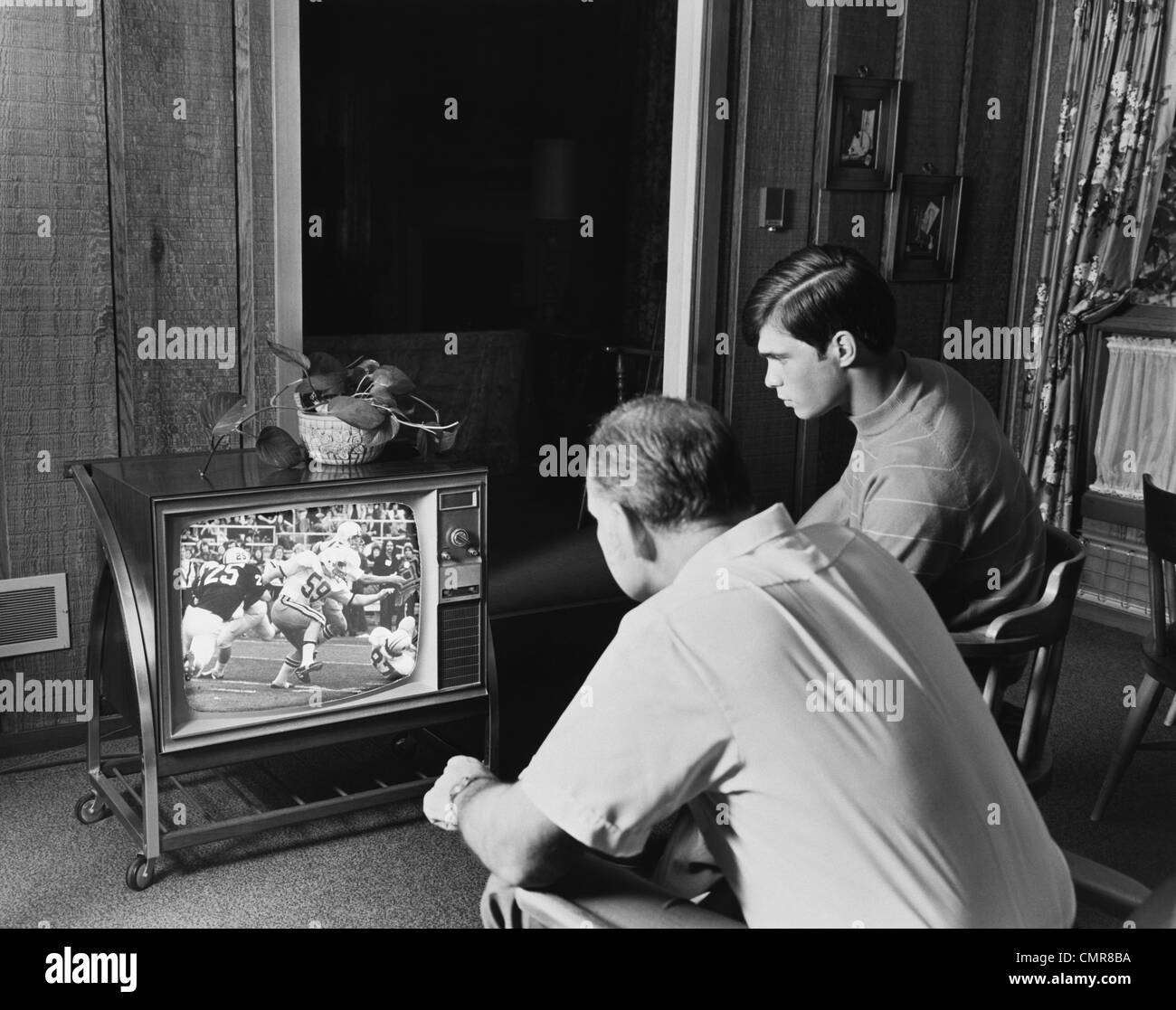 1960s 1970s TEEN BOY WATCHING FOOTBALL GAME ON TELEVISION WITH ADULT DAD - Stock Image