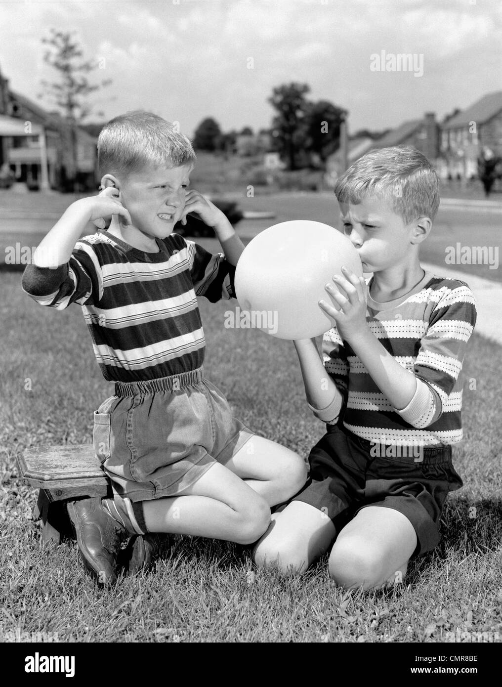 1950s TWO YOUNG BOYS ONE BLOWING UP BALLOON ONE WITH FINGERS IN EARS AFRAID OF EXPLOSION - Stock Image