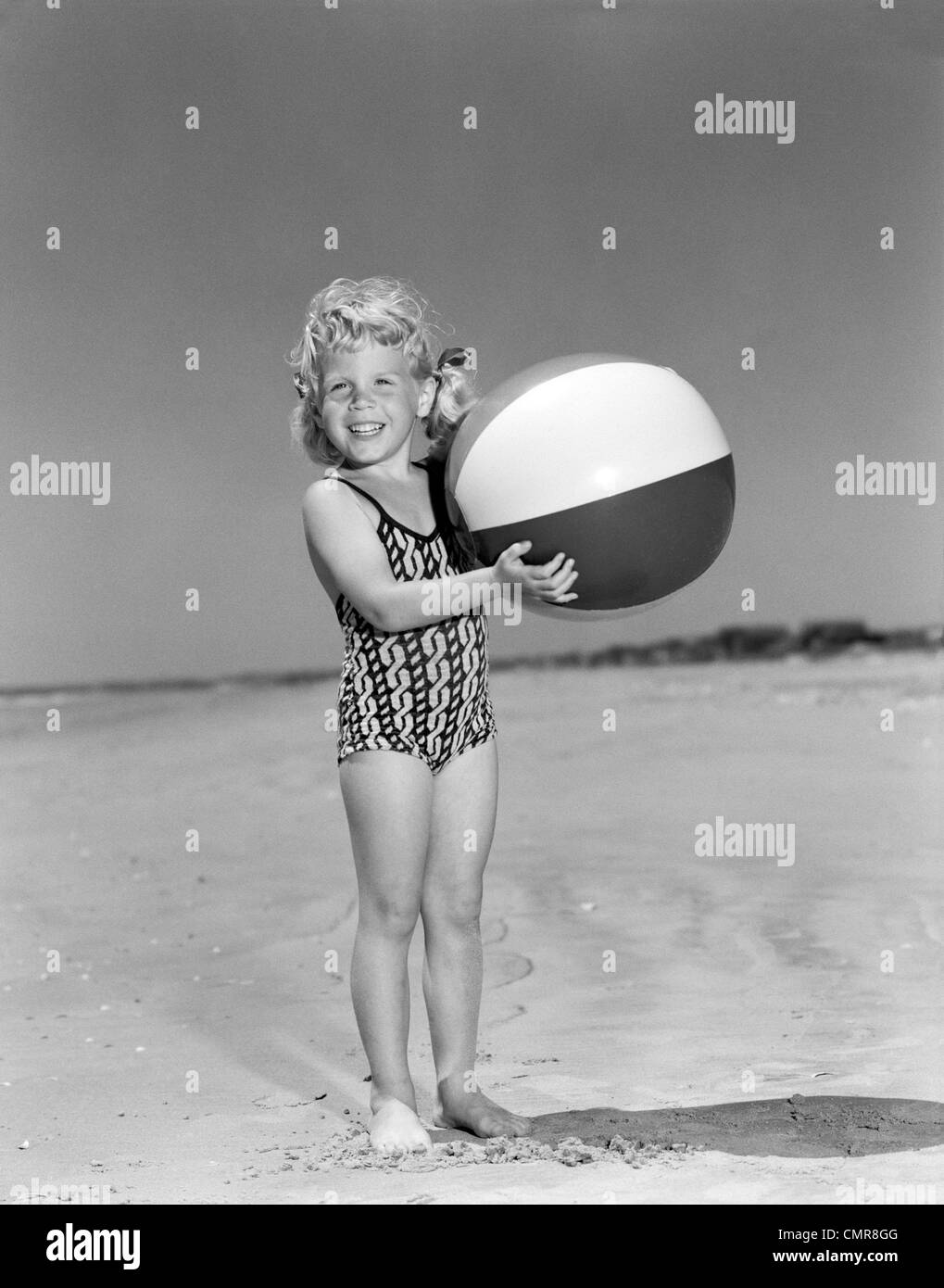 1950s SMILING LITTLE GIRL STANDING ON BEACH HOLDING BEACH BALL LOOKING AT CAMERA - Stock Image