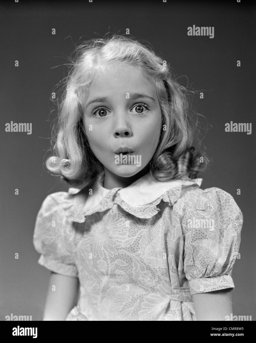 1940s 1950s BLOND GIRL WHISTLING LIPS PUCKERED EYES WIDE OPEN LOOKING AT CAMERA - Stock Image