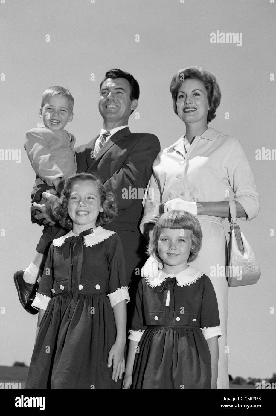 1960s PORTRAIT SMILING FAMILY FATHER MOTHER TWO DAUGHTERS SON STANDING TOGETHER OUTDOORS - Stock Image