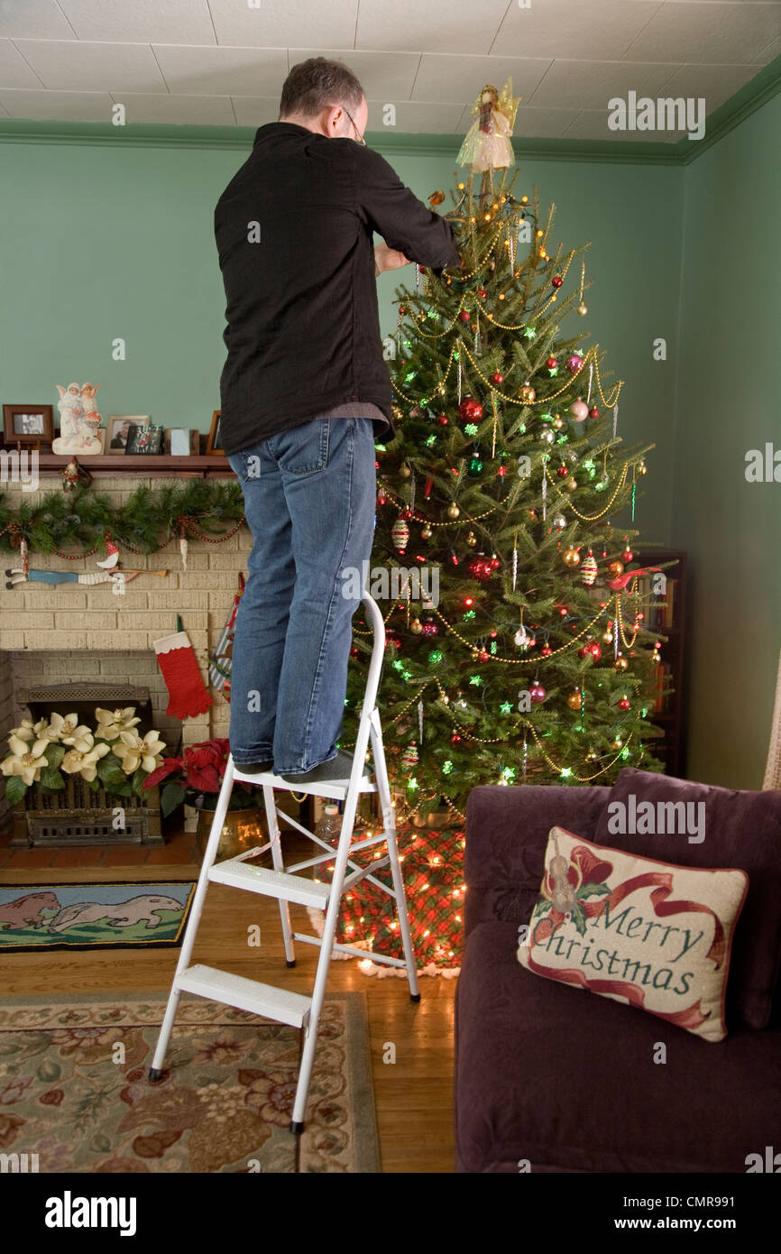 man standing on a ladder decorating the christmas tree whitby ontario stock image - Christmas Tree Ladder Decoration