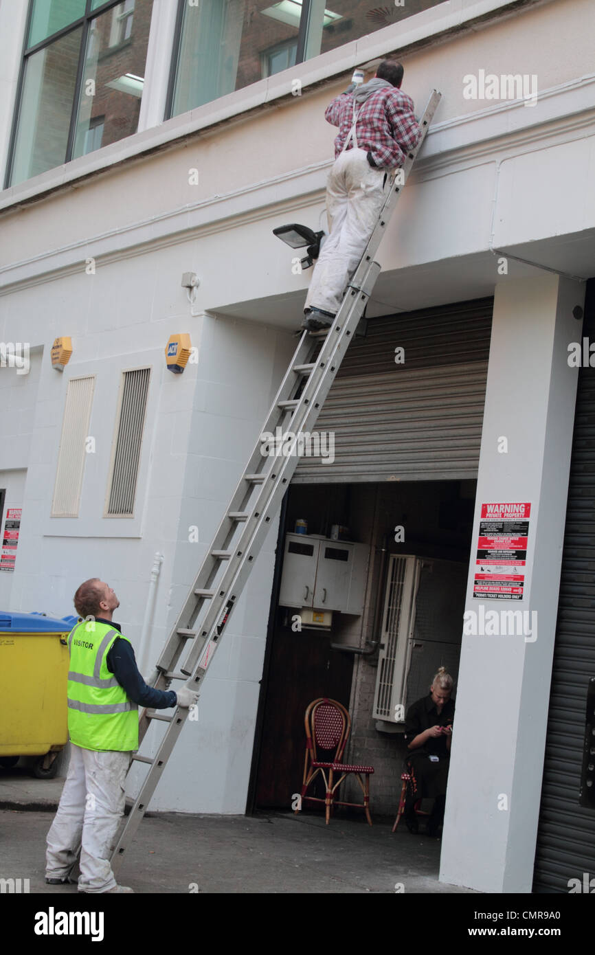 Man painting while up a ladder;while colleague holds the ladder. - Stock Image