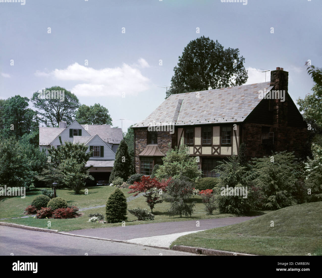 1950s STREET SUBURBAN COMMUNITY STONE TUDOR STYLE UPSCALE HOUSE - Stock Image