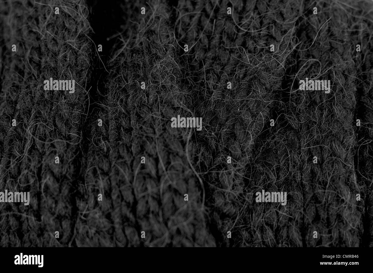 Rough heavy wool knitted and layered texture. Black and white photo. Select focus. - Stock Image