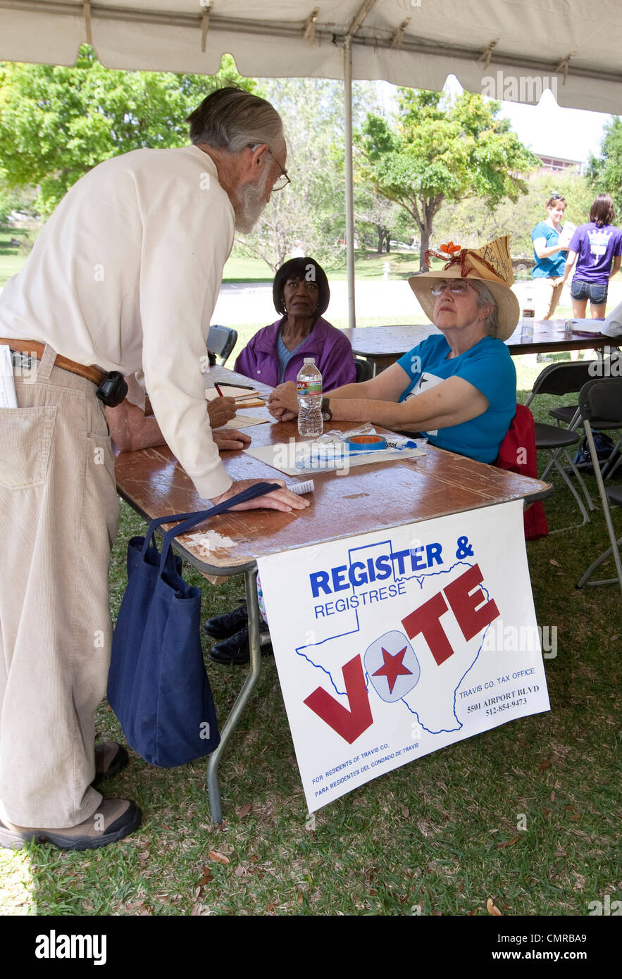 Female worker tends to a voter registration table trying to lure potential voters to sign up including senior citizens - Stock Image