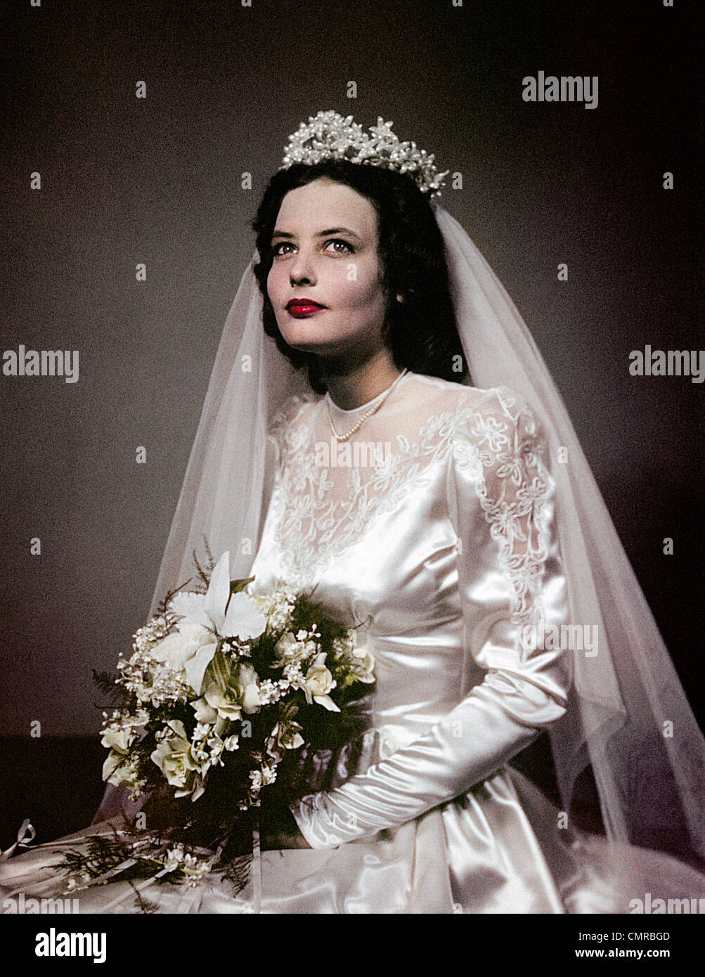 1940s 1950s PORTRAIT BRUNETTE BRIDE IN BRIDAL GOWN WITH FLOWER BOUQUET - Stock Image