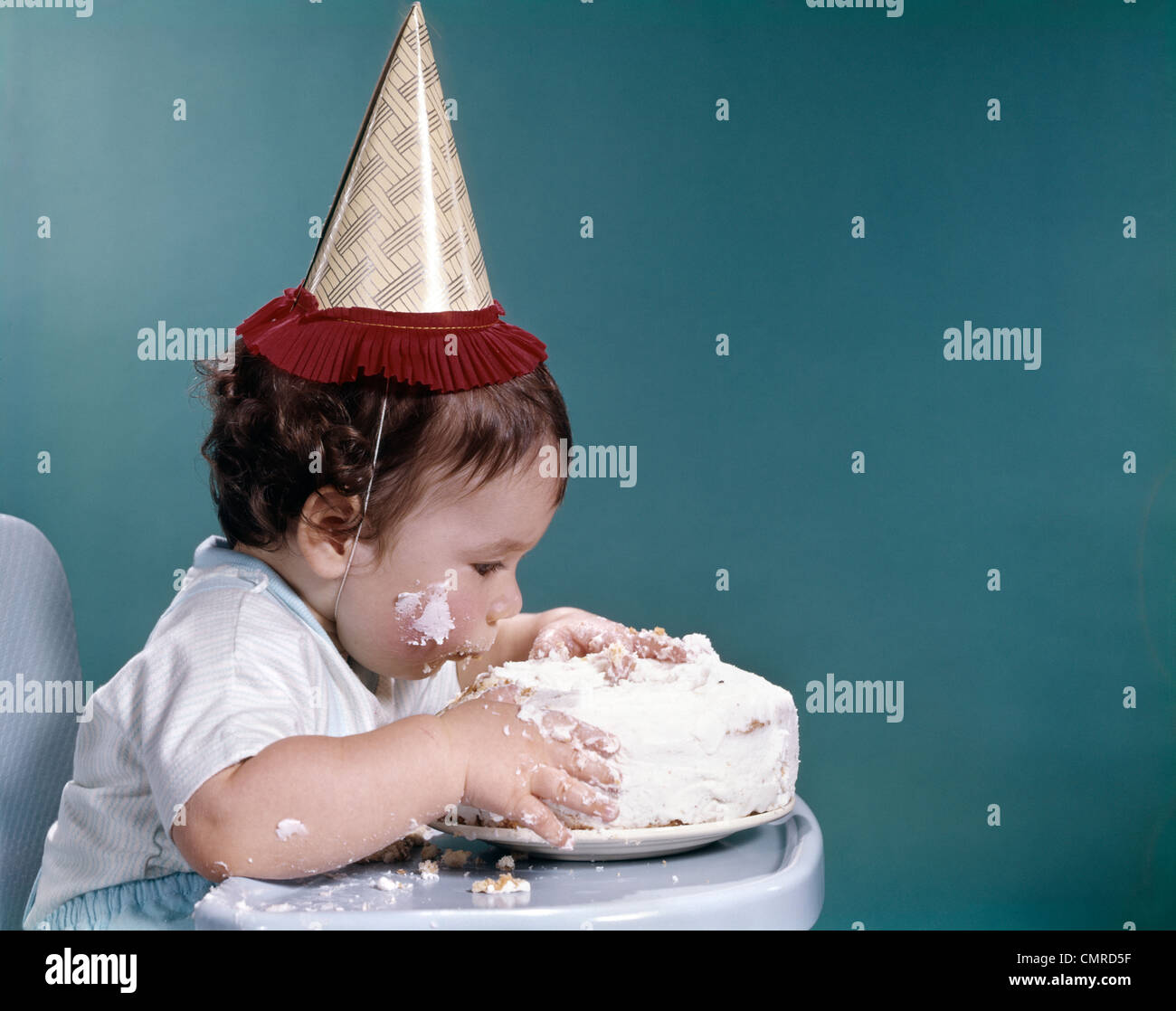 1960s Baby In Highchair Wearing Birthday Hat Eating Whole Birthday