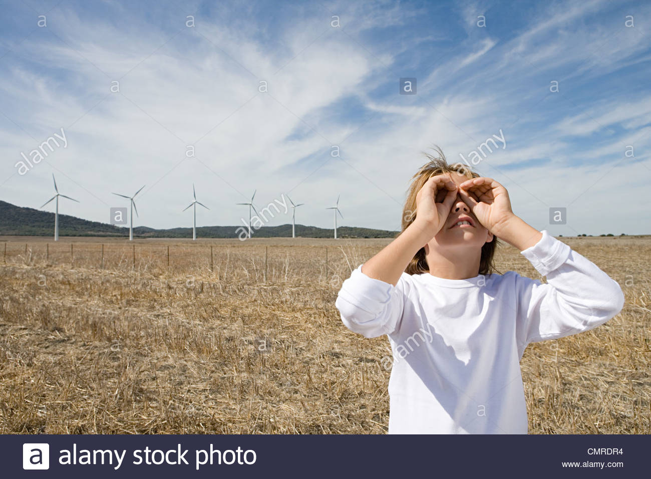 Boy in a field with wind turbines - Stock Image
