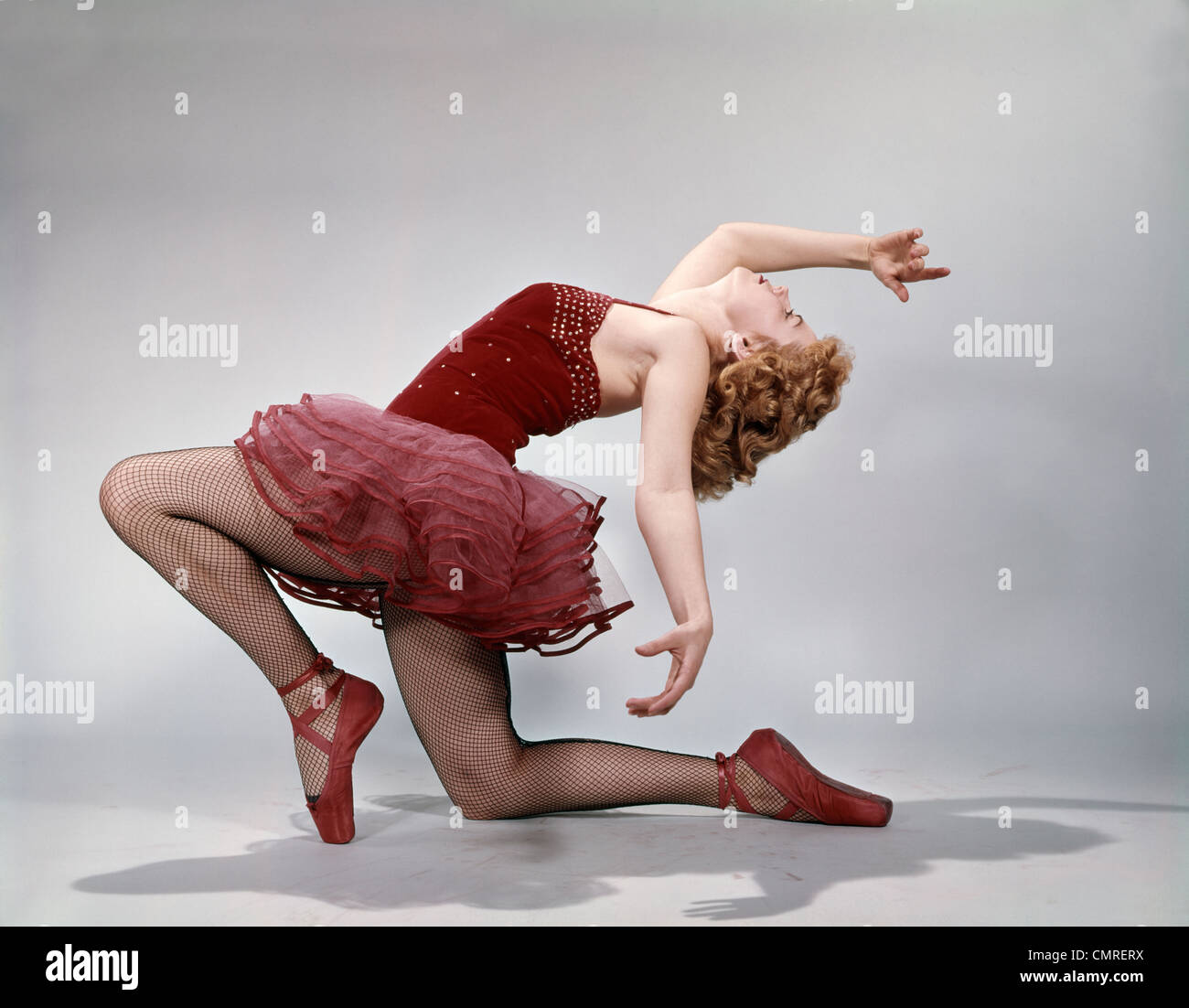 1960s TEEN GIRL LAYBACK POSITION RED VELVET COSTUME PINK NET TUTU BALLET ATTITUDE - Stock Image