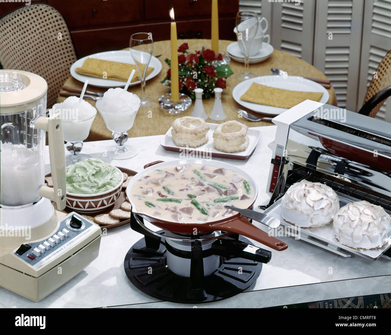 1970s STILL LIFE BLENDER FROZEN DAIQUIRI AVOCADO DIP HAM CASSEROLE MERINGUE TARTS TABLE SET FOR DINNER FOR TWO - Stock Image