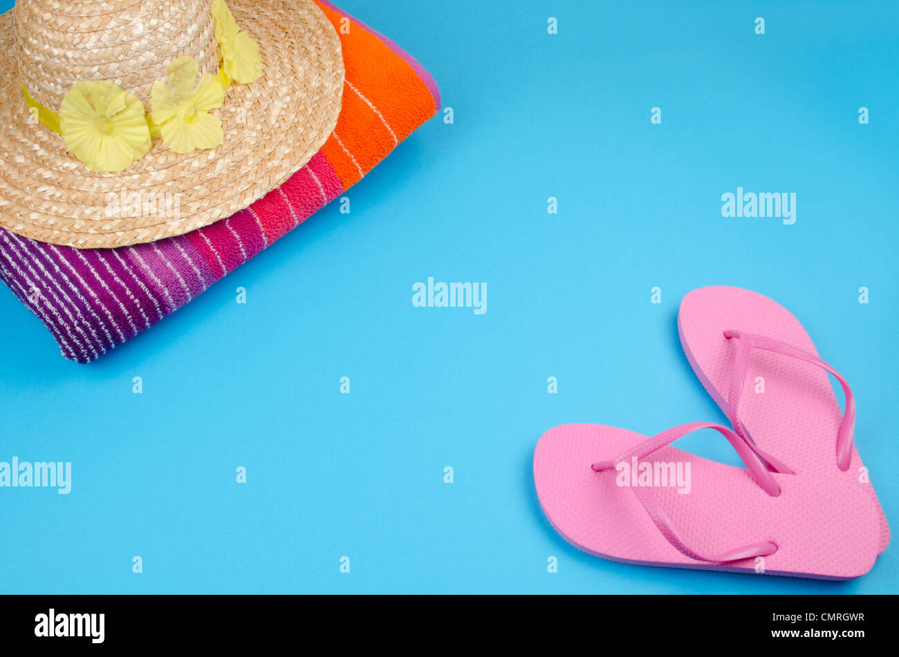 47fa3c0a0ae7c1 Pink flip-flops on a blue background with a sun hat and beach towel -