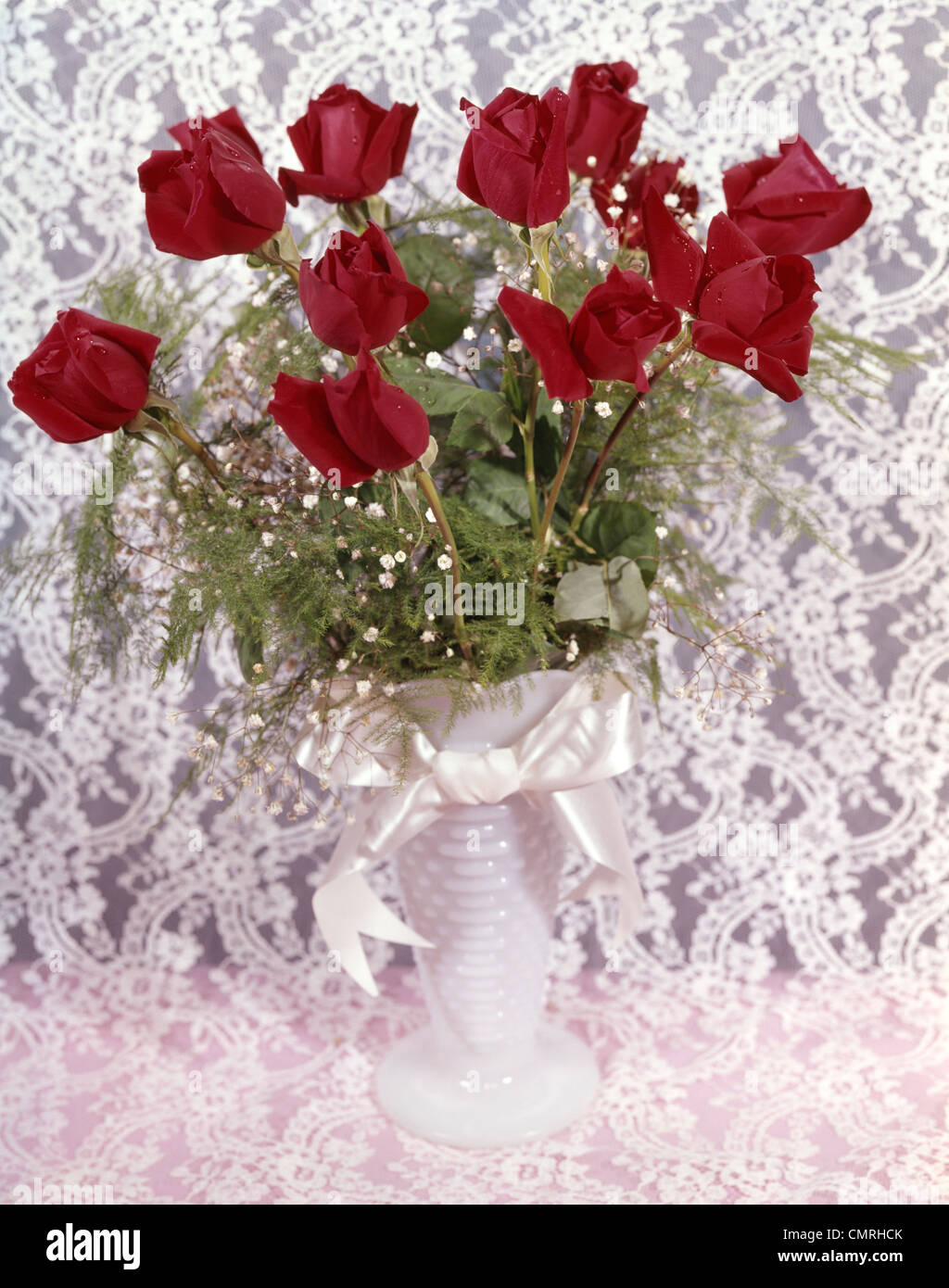 1960s 1970s STILL LIFE BOUQUET OF RED ROSES BABY'S BREATH IN WHITE VASE ON WHITE LACE - Stock Image