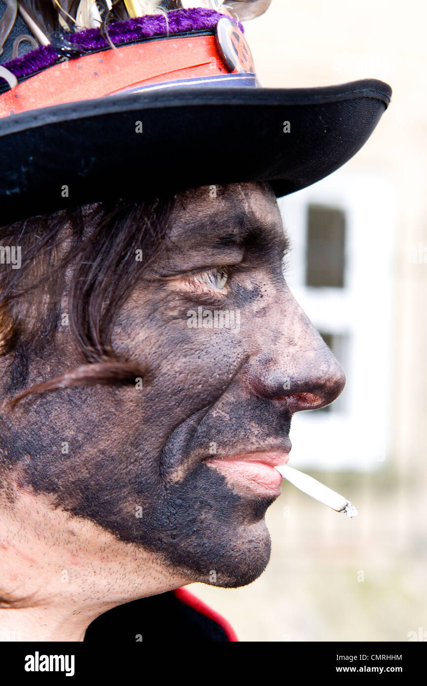 Portrait of a traditional black faced morris dancer smoking a cigarette at Bakewell Day of Dance - Stock Image