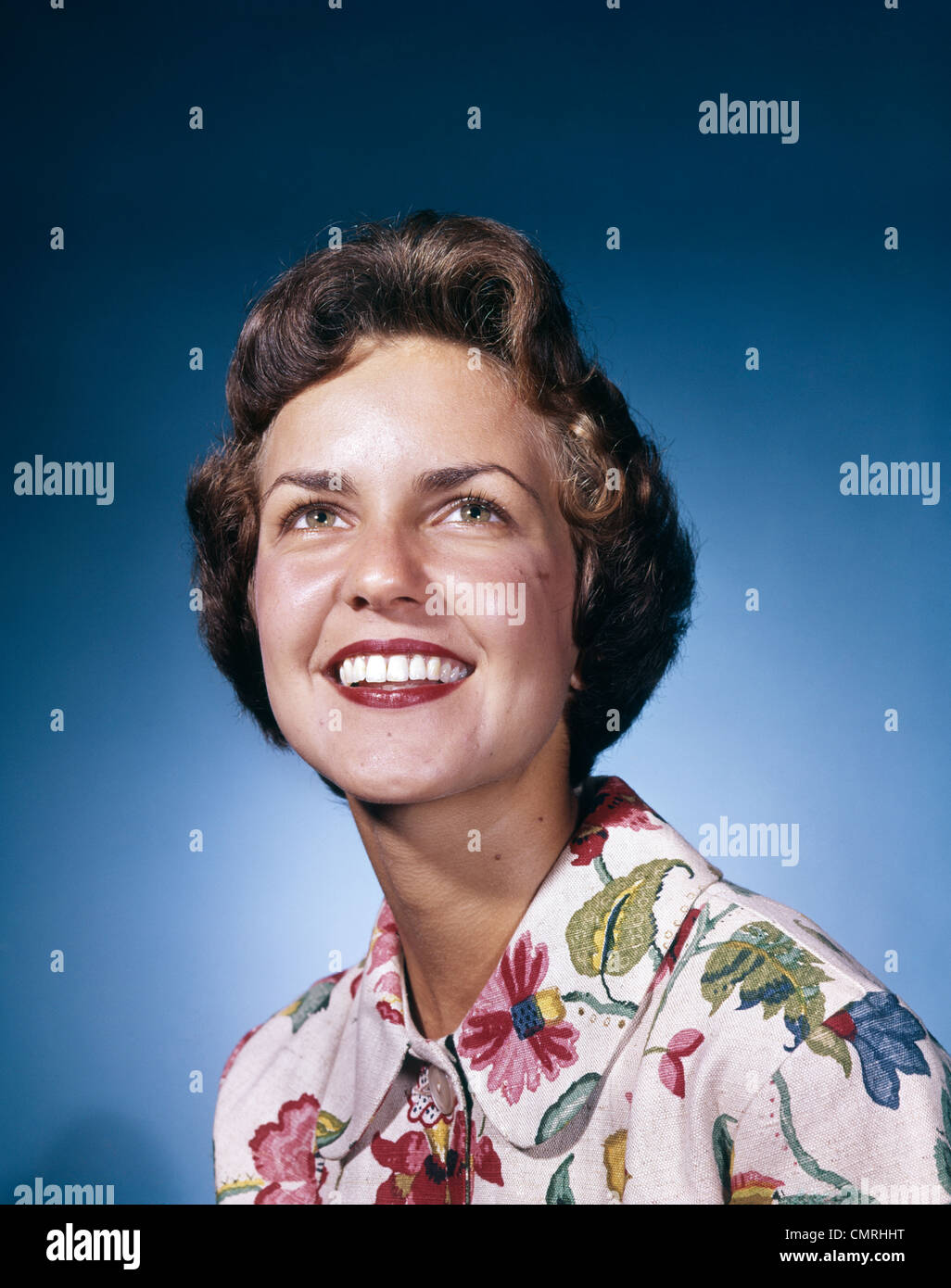 1960s SMILING WOMAN IN WHITE PRINT DRESS LOOKING UP STUDIO - Stock Image