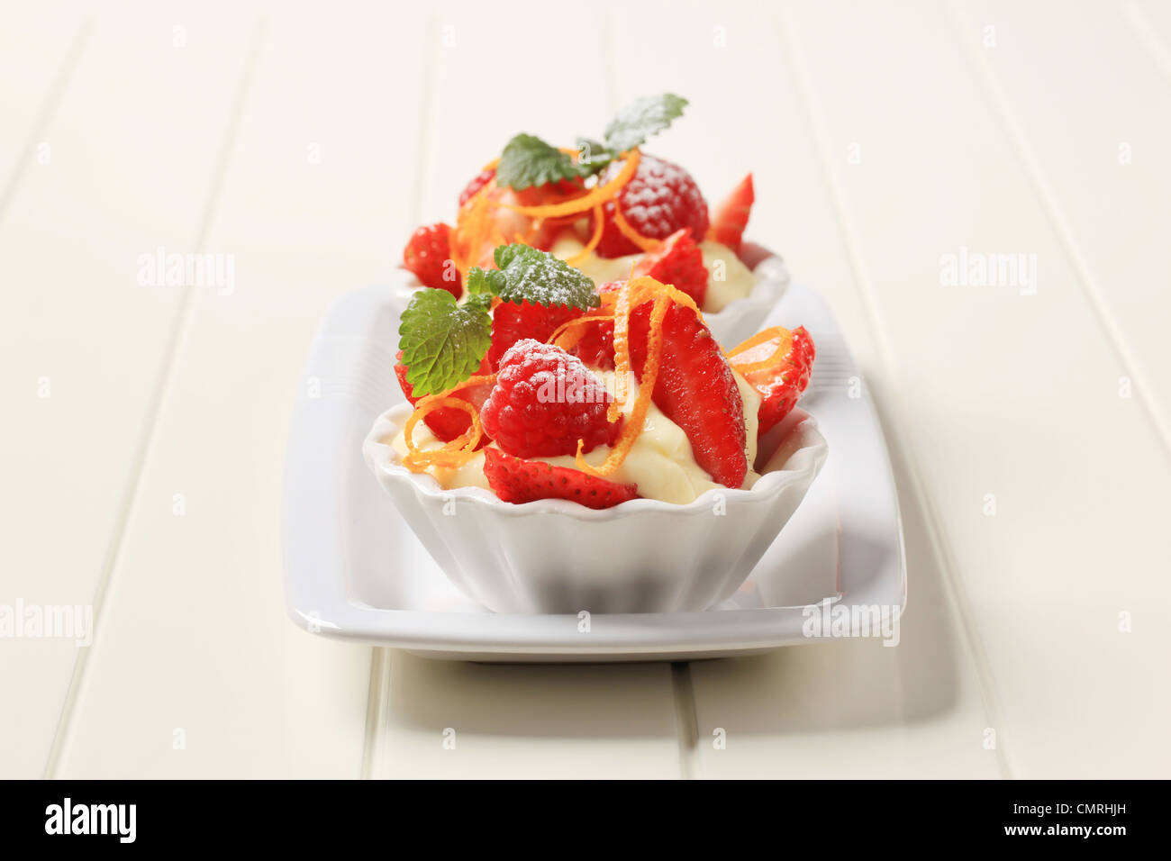 Creamy pudding and fresh fruit in small dessert dishes - Stock Image
