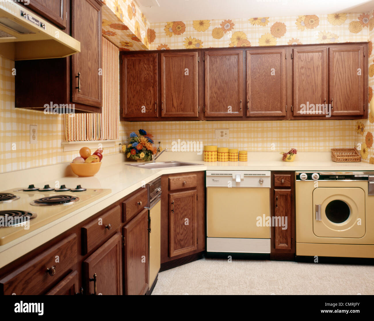 1970s KITCHEN INTERIOR WITH YELLOW APPLIANCES WOOD CABINETS AND SUNFLOWER  FLORAL PRINT WALLPAPER