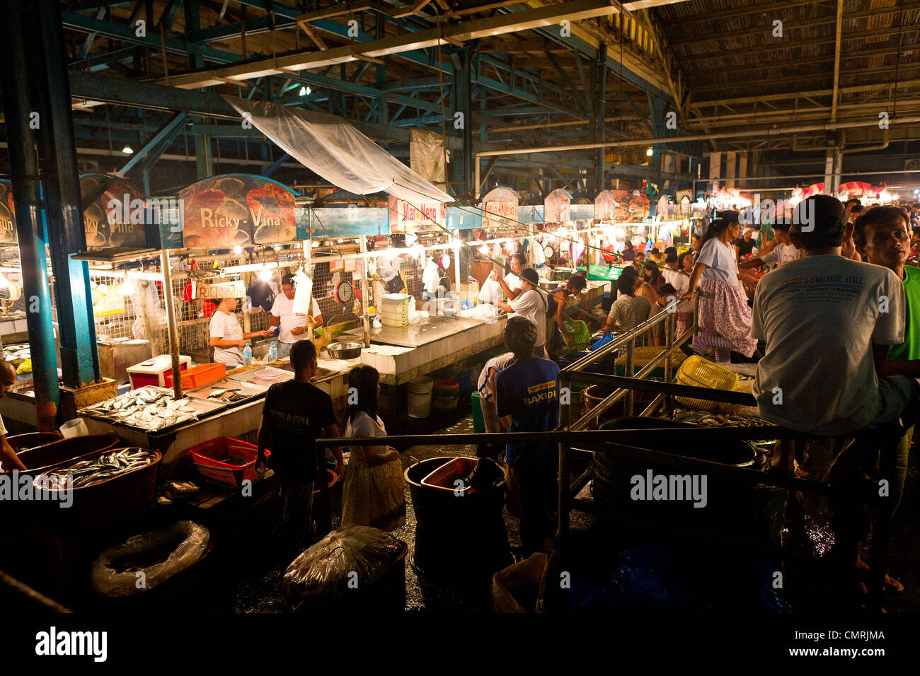Workers stock their stalls with fresh fish and seafood in the Cubao Farmer's Market, Quezon City, Manila, Philippine - Stock Image