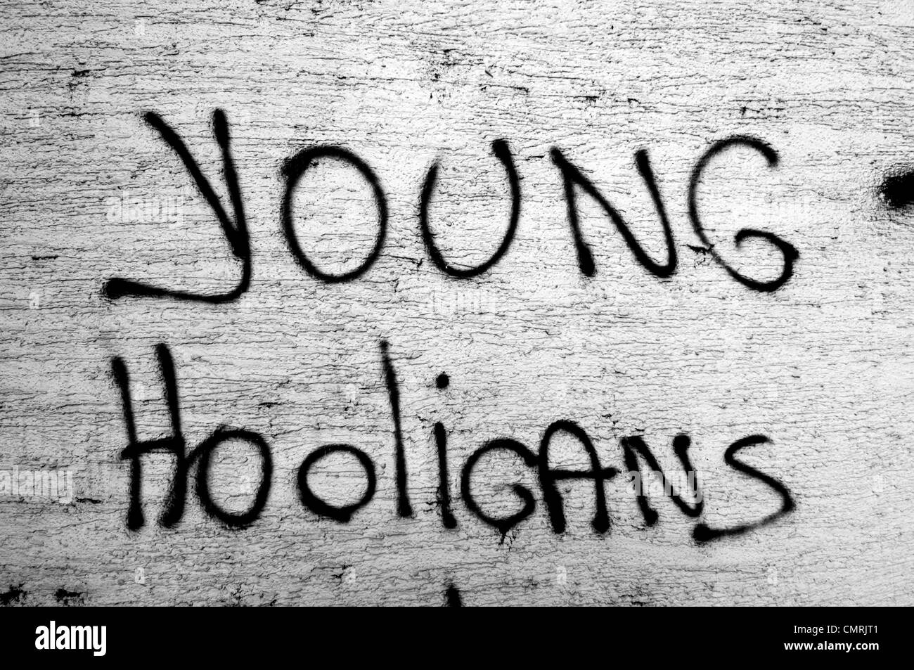 Young hooligans, black andwhite grafitti on a wall - Stock Image