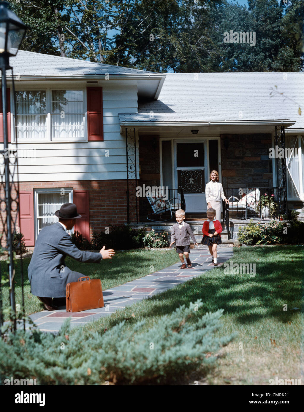 1950s FATHER COMING HOME KNEELING ARMS EXTENDED BOY GIRL RUNNING TO WELCOME HIM WOMAN STAND SUBURBAN HOUSE FAMILY - Stock Image