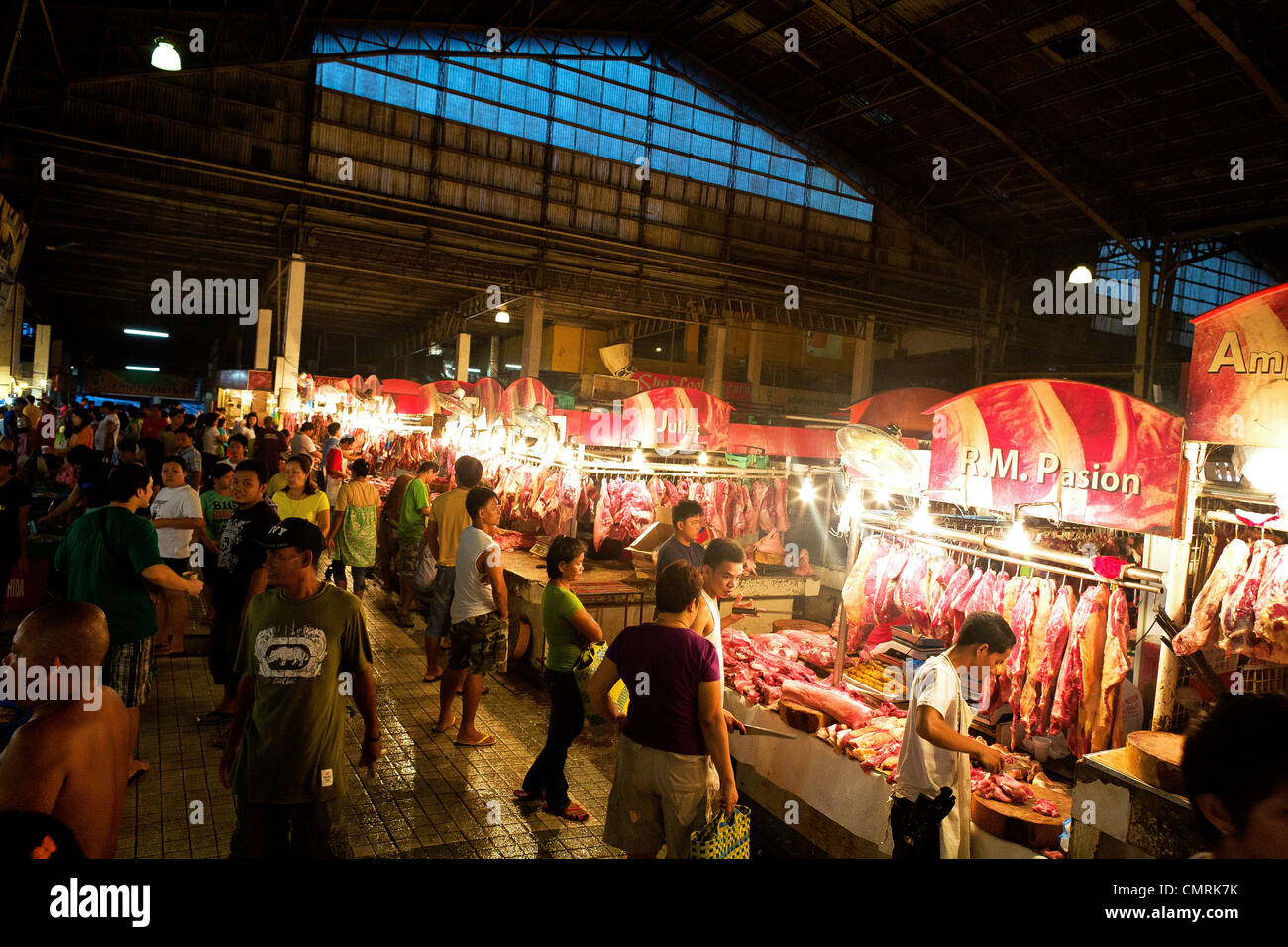 Crowds inspect the cuts of meat on display at the Cubao Farmer's Market in Quezon City, Manila, Philippine Islands. - Stock Image