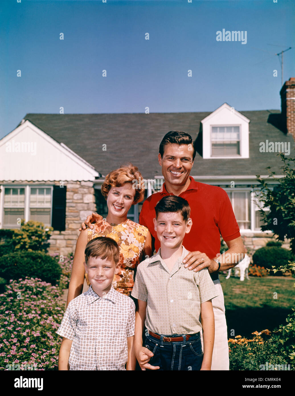 PORTRAIT SMILING FAMILY FATHER MOTHER TWO SONS STANDING TOGETHER IN FRONT OF SUBURBAN HOUSE OUTDOOR 1960s - Stock Image
