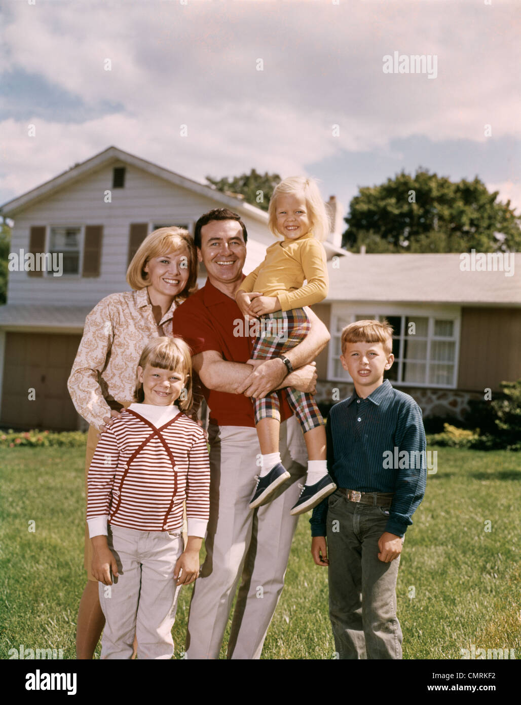 1960s FAMILY PORTRAIT STANDING IN FRONT OF A SUBURBAN SPLIT LEVEL HOUSE FATHER MOTHER TWO DAUGHTERS SON SMILING - Stock Image