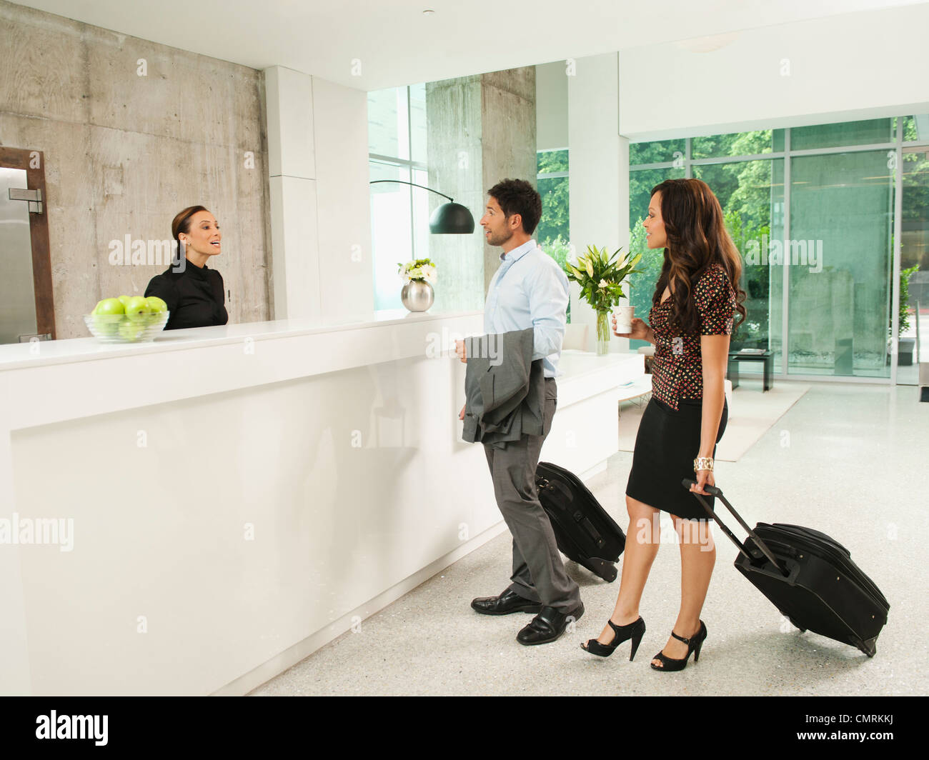 Business people arriving at hotel reception area Stock Photo