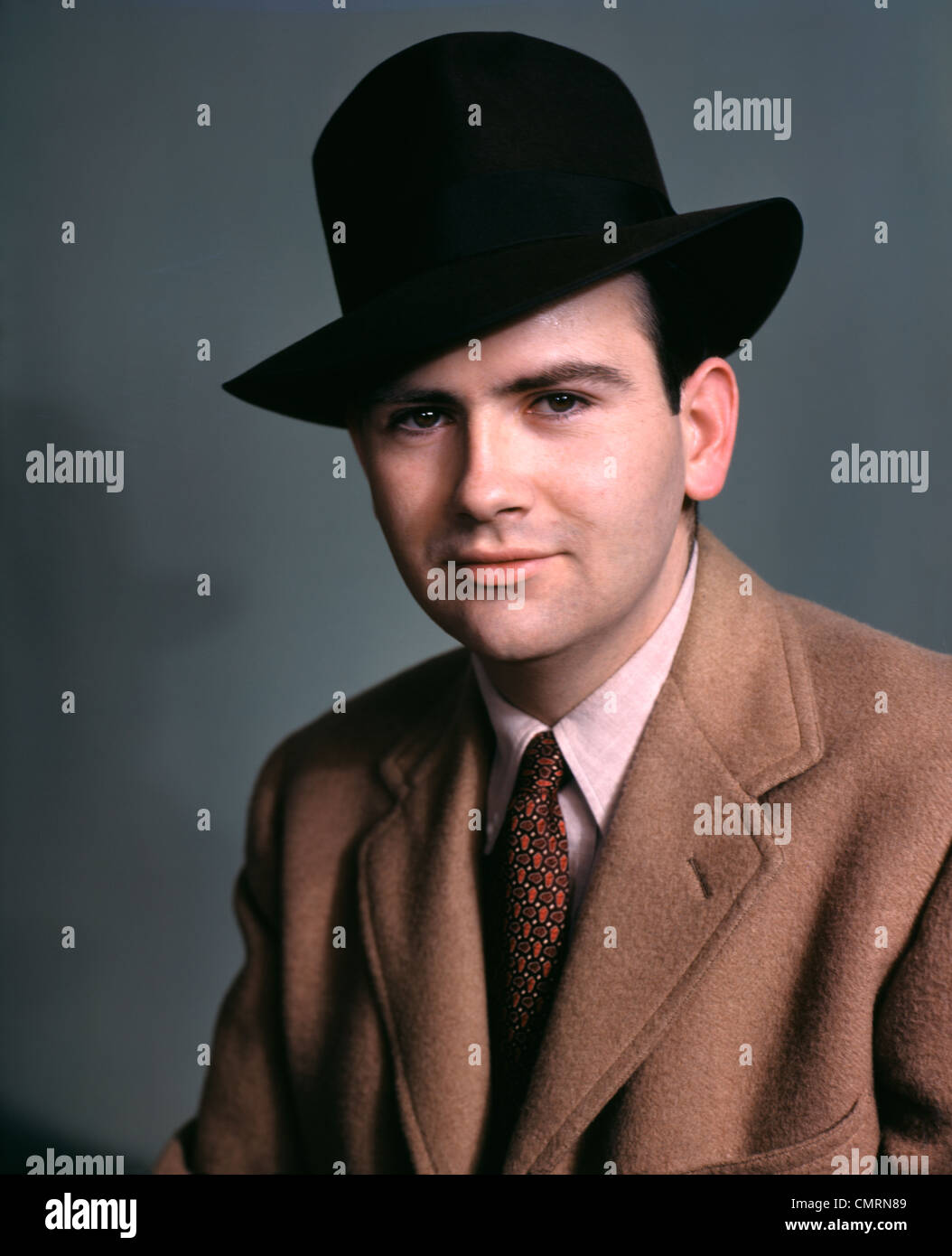 acb0d690caa70 1940s 1950s PORTRAIT FASHIONABLE YOUNG MAN WEARING BLACK FEDORA HAT CAMEL  HAIR COAT AND TIE -
