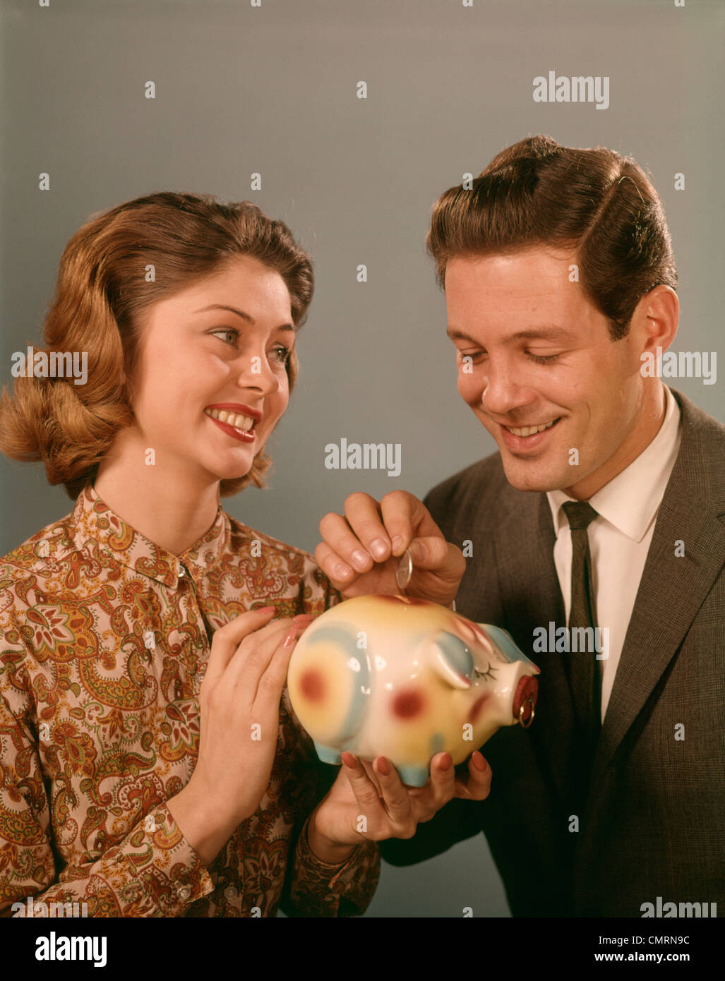 1960 1960s HAPPY SMILING COUPLE PUTTING COINS INTO PIGGY BANK PIG FINANCE MONEY SAVINGS BANKING SAVING COUPLES RETRO - Stock Image
