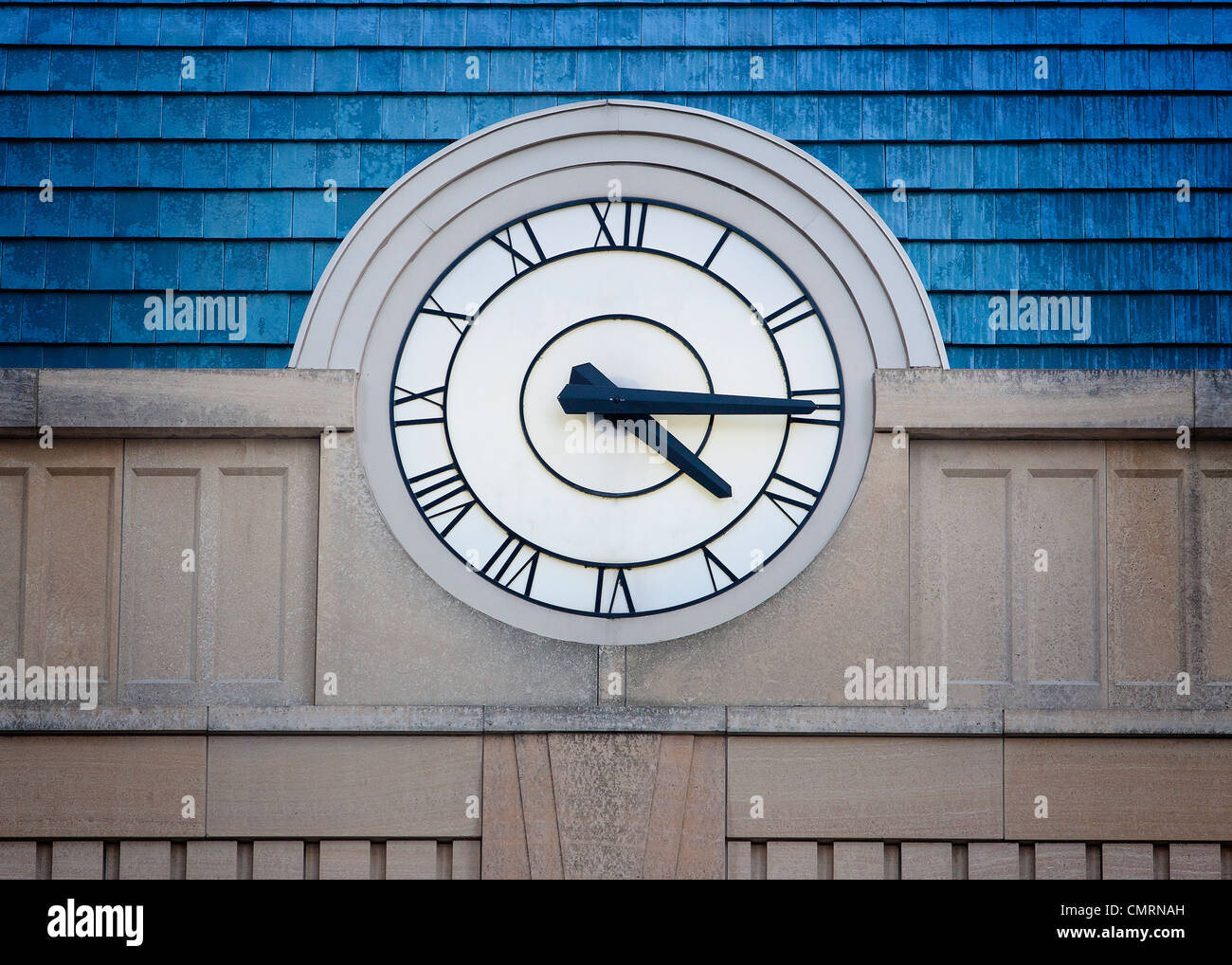 Big outside clock with Roman Numerals on stone building with blue roof - Stock Image